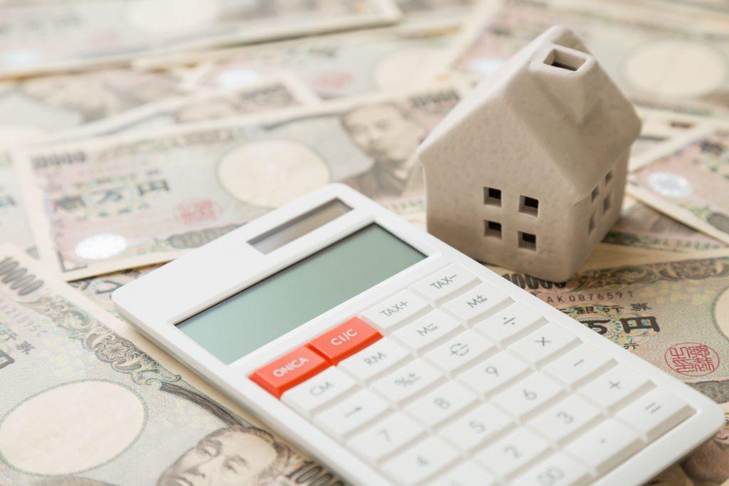 お金と電卓と家の模型