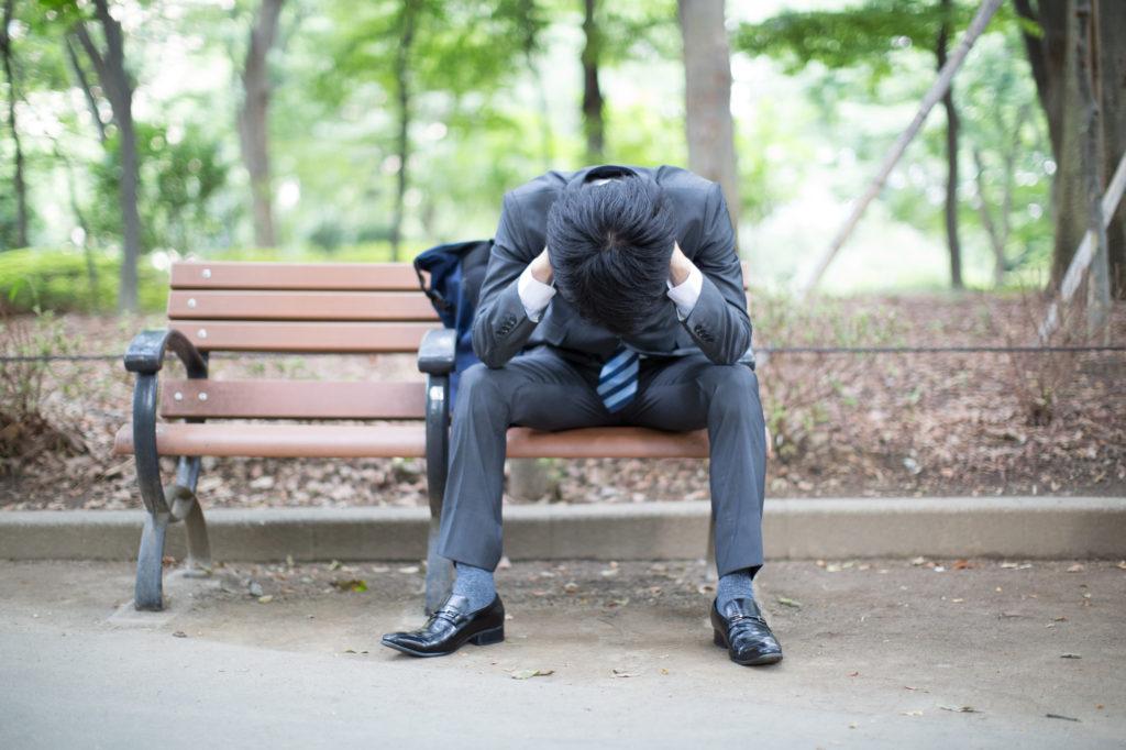 ベンチで頭を抱え込む男性